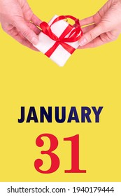 January 31st. Festive Vertical Calendar With Hands Holding White Gift Box With Red Ribbon And Calendar Date 31 January On Illuminating Yellow Background. Winter month, day of the year concept.