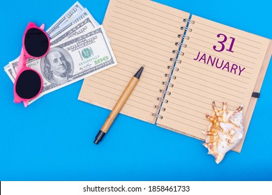 January 31st. January 31st. Travel plan flat design with notepad written date, pen, glasses, money dollars and seashell on blue background. Winter month, day of the year, calendar concept