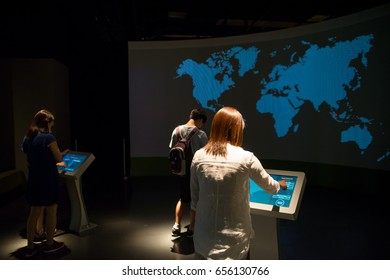 January 5, 2017. Tourists interact with a projected display showing a blue, pixelated, world map at the Singapore National Museum. Travel and technology editorial concept.