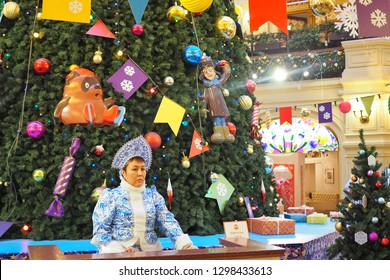 January 5, 2019 - Moscow, Russia. Sad saleswoman of ice cream on the background of big Christmas tree and no buyers at State Department Store (GUM)