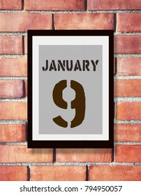 January 9th. 9 January calendar on the wood photo frame with brown brick background. Winter day.