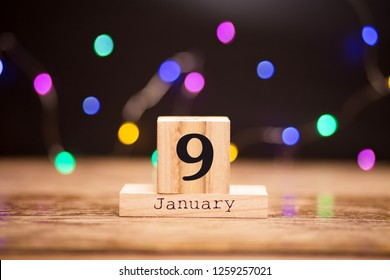 January 9th. Day 9 of January set on wooden calendar on dark background with garland bokeh. Winter time.