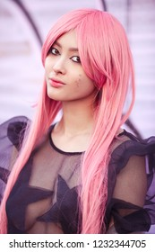 Japan anime cosplay. Colorful portrait of young attractive asian woman in sexy dress with creative make-up and wearing pink wig outdoors. Trendy Japanese girl walking outside on city street. Cool