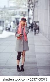 Japan anime cosplay. Colorful portrait of young attractive smiling asian woman in coat with creative make-up wearing pink wig. Trendy Japanese girl using smartphone listening musik in earphones