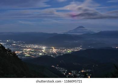 """Japan beautiful landscape of Mountain Fuji and night view of Koofu City from """"KUSHIGATA"""" mountain path, Japan - Sep. 22, 2018."""