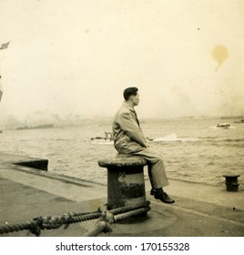 JAPAN  - Circa 1950s: An antique photo shows man sitting on a bollard on the dock watching the sea