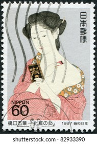 "JAPAN - CIRCA 1987: A stamp printed in Japan, shows a painting ""Woman Applying Powder"" by Hashiguchi Goyo, circa 1987"