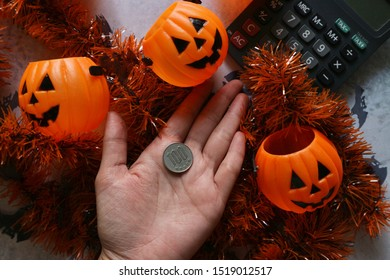 Japan coin money on hand with pumpkin smile face buckets, calculator and Halloween decorations ribbons on marble pattern table