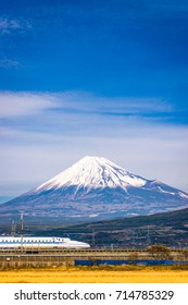 JAPAN - DECEMBER 14, 2012: A Shinkansen bullet train passes below Mt. Fuji in Japan.