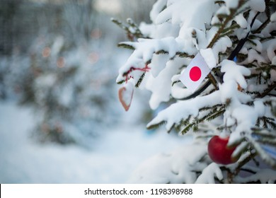 Japan flag. Christmas background outdoor. Christmas tree covered with snow and decorations and Japanese flag. New Year / Christmas holiday greeting card.