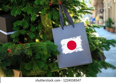 Japan flag printed on a Christmas shopping bag. Close up of a gift bag as a decoration on a Xmas tree on a street. New Year or Christmas shopping, local market sale and deals concept.