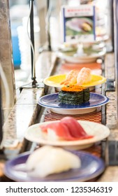 japan Food on conveyor or belt buffet of sushi in restaurant with blurred background.