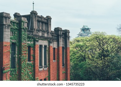 Japan Mint Museum old history building with red brick wall full of vine. monument in japan with osaka castle in background far away long distance under blue sky. spring forest with green trees.