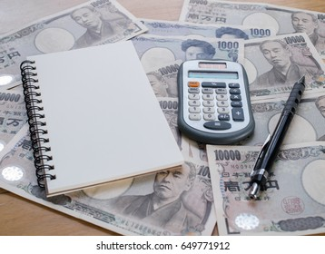 Japan money - Calculator, Notebook and pencil on Japanese yen currency