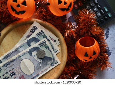 Japan money and coin on wood tray with calculator, pumpkin head bucket, Halloween ribbons decorations on marble table