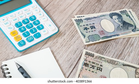 Japan money - Japanese yen currency and Calculator, notebook, pencil on wooden background
