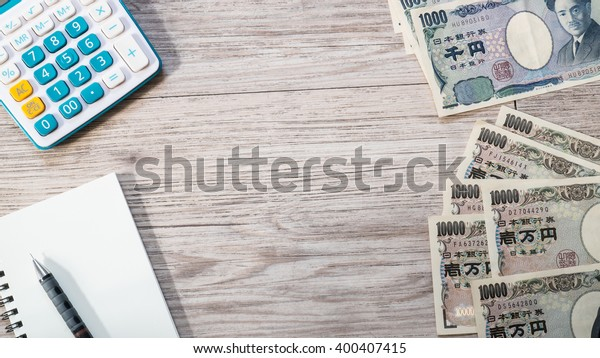 Japan money - Japanese yen currency and Calculator, notebook, pencil on wooden background ( Space and composition for text )