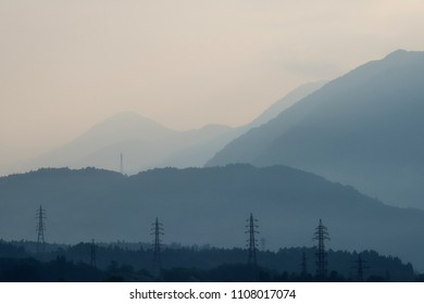 In Japan, the morning and a scenic beautiful view of mountains against the sunlight, electrical pylon and fog.