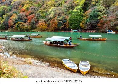 Japan - November 26, 2019 : Japanese Boatman punitng Katsura Tourist Sightseeing Boats taking Tourist along Hozugawa River with Colourful Maple Tree in Autumn, Arashiyama, Kyoto