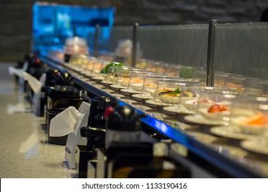Japan restaurant sushi conveyor or belt buffet. belt sushi in japan restaurant with blurred background.