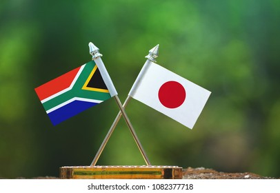 Japan and South Africa small flag with blur green background