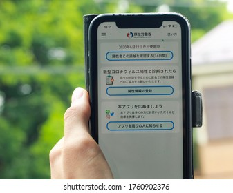 Japan, Tokyo - June 22, 2020 - Caucasian hand holding smartphone with the Japanese corona contact tracing app outside. The app is available in Japan since June 19.