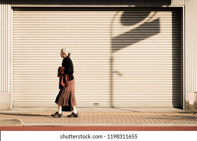 JAPAN, TOKYO - NOVEMBER 2016: An unidentified old woman walks along the roadside of Tokyo, Japan. Japan's population is aging.