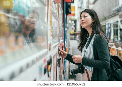 Japan vending machine. Young female tourist choosing a snack or drink at vending machine. lady putting coins into the vendor machine on the japanese street.