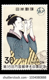 "JAPAN-CIRCA 1969: Canceled Japanese stamp of ""Woman Reading a Letter"" by Kitagawa Utamaro, an late  18-century Japanese ukiyo-e woodblock artist, depicting a woman in a blue and gold kimono, reading a"