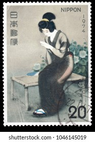 "JAPAN-CIRCA 1974: Canceled Japanese stamp of ""Finger"" by Shinsui Ito, an artist of early 20th-century Japan. The painting captures a Japanese woman in dark modern dress on a bench."
