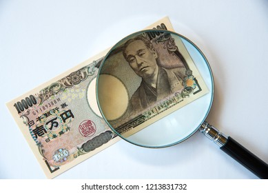 Japanese 10K bank note under magnifying glass