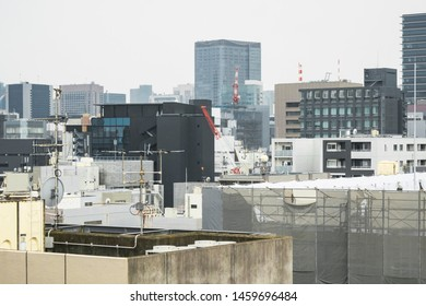 Japanese abstract urban background featuring details of chaotic city buildings and skyline in Tokyo downtown in Ginza district at daytime in July rain season.