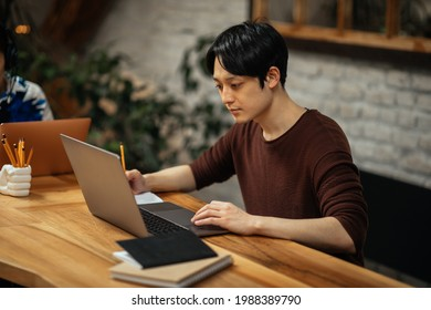 Japanese adult male drinking coffee and working via technology while sitting at the kitchen table