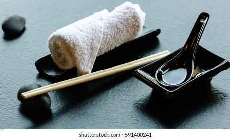 Japanese, asian food utensils - pair of chopsticks, hot weat towel, ceramic black spoon, dark stone in restaurant, cafe.