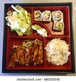 A Japanese Bento Box with rice, sushi, vegetables, and teriyaki chicken.  Bento boxes are popular for their proportions and value