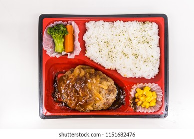 A Japanese Bento Box with rice, vegetables, and teriyaki chicken. Bento boxes are sale in convenience store and train. Japanese food from top view, selected on white background.