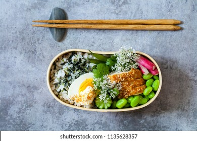 Japanese bento lunch box with sesame crusted chicken, edamame beans, egg and spicy rice
