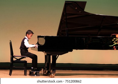 Japanese boy playing piano on stage (second grade at elementary school)