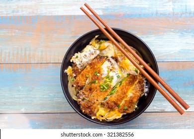 Japanese breaded deep fried pork with egg name is Katsudon in black plate