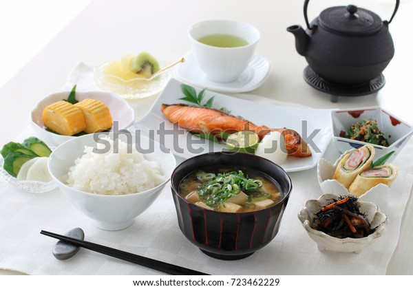Japanese breakfast with rice, miso soup,grilled salmon,rolled omelet and some small bowls