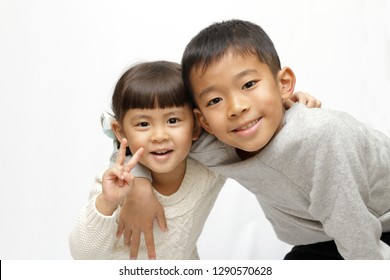 Japanese brother and sister putting arms around each other's sholders (9 years old boy and 4 years old girl)