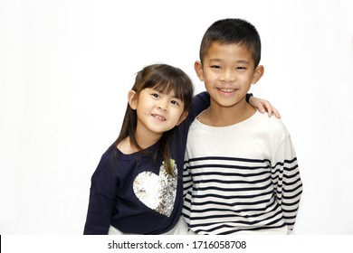 Japanese brother and sister putting arms around each other's sholders (10 years old boy and 5 years old girl)