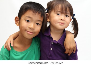 Japanese brother and sister putting arms around each other's sholders (8 years old boy and 3 years old girl)