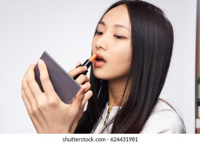 Japanese brunette woman colors lipstick lips