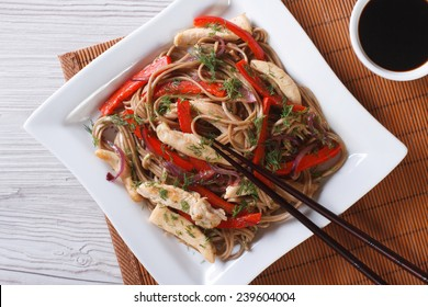 Japanese buckwheat soba noodles with chicken and vegetables on a plate close-up. horizontal view from above