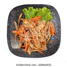 Japanese burdock root, gobo root salad on black plate, isolated on white background