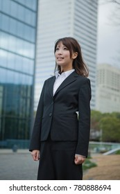 Japanese business woman standing in front of the building
