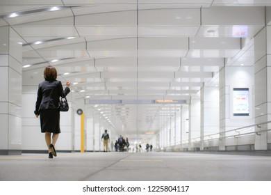Japanese business woman walking underground in Tokyo.