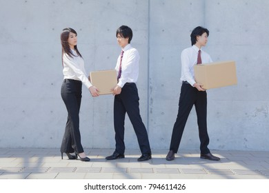 Japanese businessmen and businesswomen carrying a cardboard