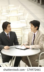 Japanese businessmen sitting at a table having a meeting